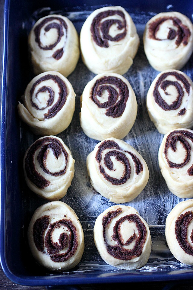 These are the BEST Chocolate Breakfast Rolls EVER! Super fluffy and a treat to bite into – These rolls are filled with a sweet chocolate filling and are liberally drizzled with a cocoa glaze! Perfect for an indulgent breakfast! www.mind-over-batter.com