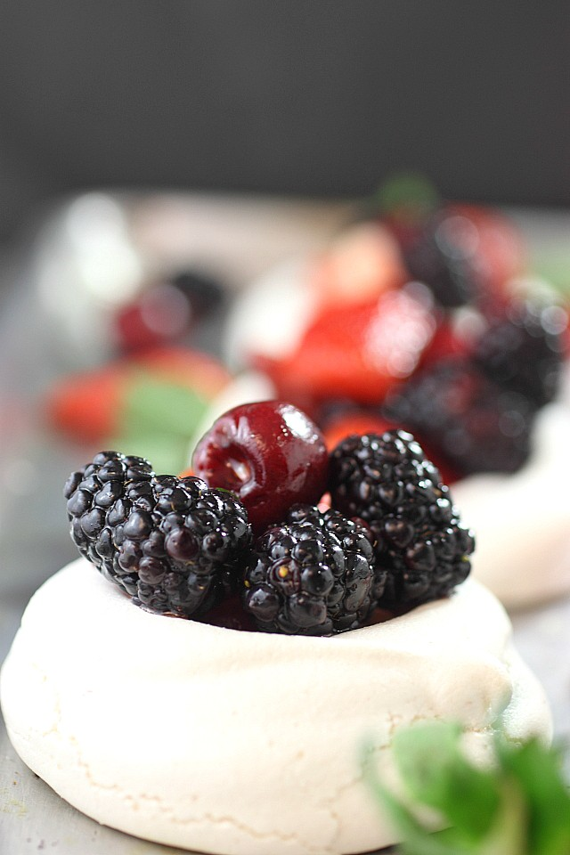 Impress your friends with these Mini Mixed Berry Pavlovas! Mini mounds of vanilla bean flavored meringue are piled with lightly sweetened berries. So pretty and so easy to make! www.mind-over-batter.com